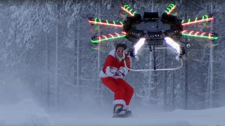 Ein Snowboarder lässt sich von einer Drone eine Skipiste herunterziehen