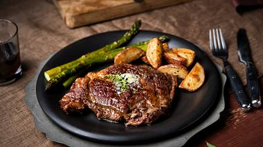 Grüner Spargel mit Pfeffersteak und Kartoffelspalten - Foto: iStock / NightAndDayImages