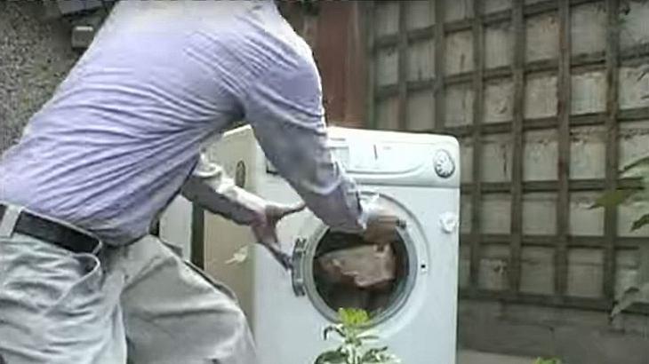 Ein Mann wirft einen Ziegelstein in eine Waschmaschine
