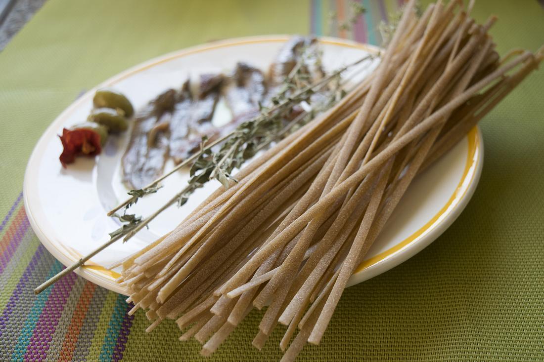 Stroncatura-Nudeln auf einem Teller. Dazu Anchovis