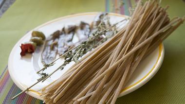 Stroncatura-Nudeln auf einem Teller. Dazu Anchovis - Foto: iStock / sal61