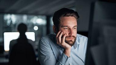 Mann sitzt lustlos im Büro vor seinem Computer - Foto: iStock / shapecharge