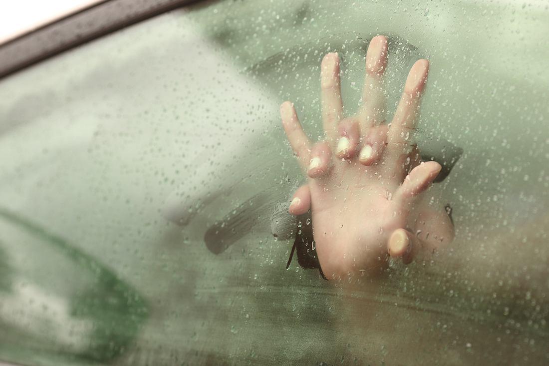 Hände an beschlagener Autoscheibe