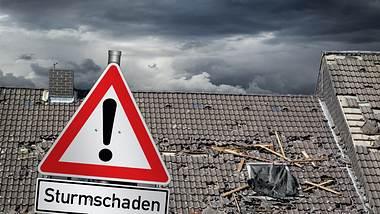 Teilweise abgedecktes Hausdach, davor ein Warnschild: Sturmschaden - Foto: Getty Images / Grafner