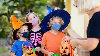 Kinder bekommen Süßigkeiten an Halloween - Foto: iStock / FamVeld