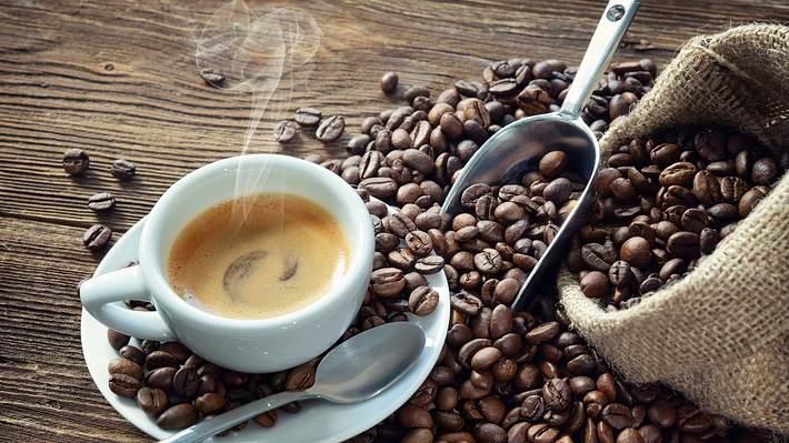 Dampfende Tasse Kaffee, mit einem offenen Sack Kaffeebohnen - Foto: Getty Images / AlexRaths