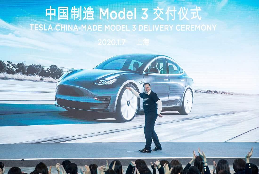 Elon Musk auf Bühne vor Bild eines Tesla Model-3