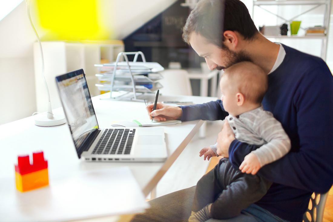 Vater mit Baby im Home Office