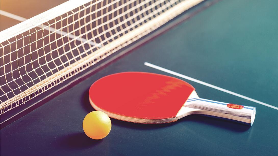 Ein Schläger und ein Ball liegen auf einer gekauften Tischtennisplatte - Foto: iStock/artisteer