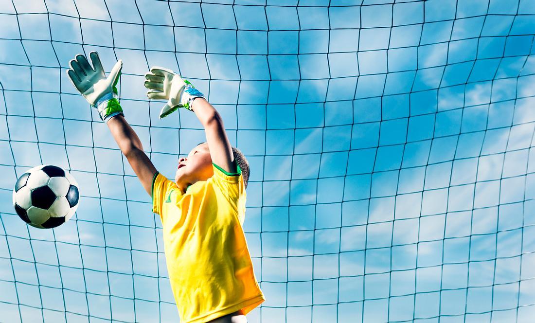 Ein Junge hält einen Ball im Tor ab und trägt dazu Torwarthandschuhe für Kinder