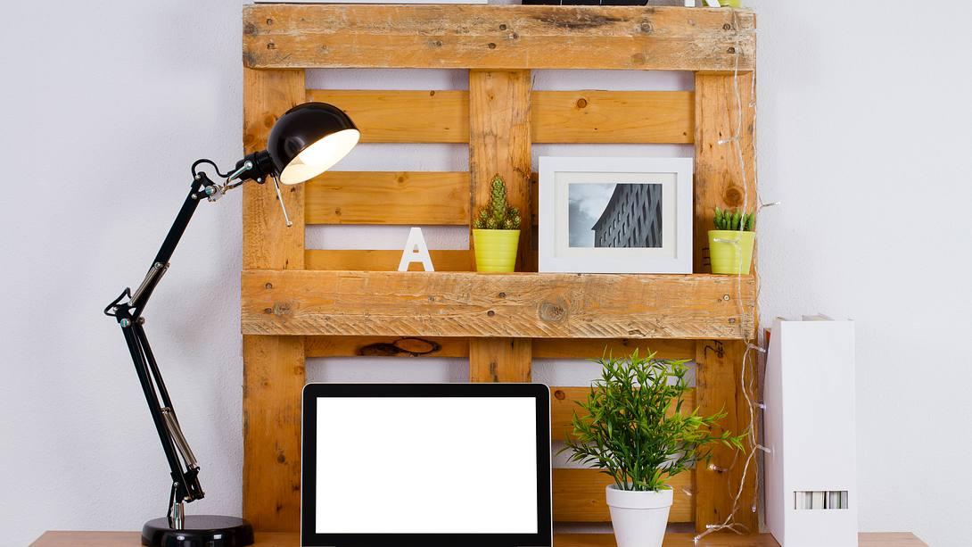 Schreibtisch mit Laptop, Holzpaletten und weiteren Utensilien - Foto: iStock / kinemero