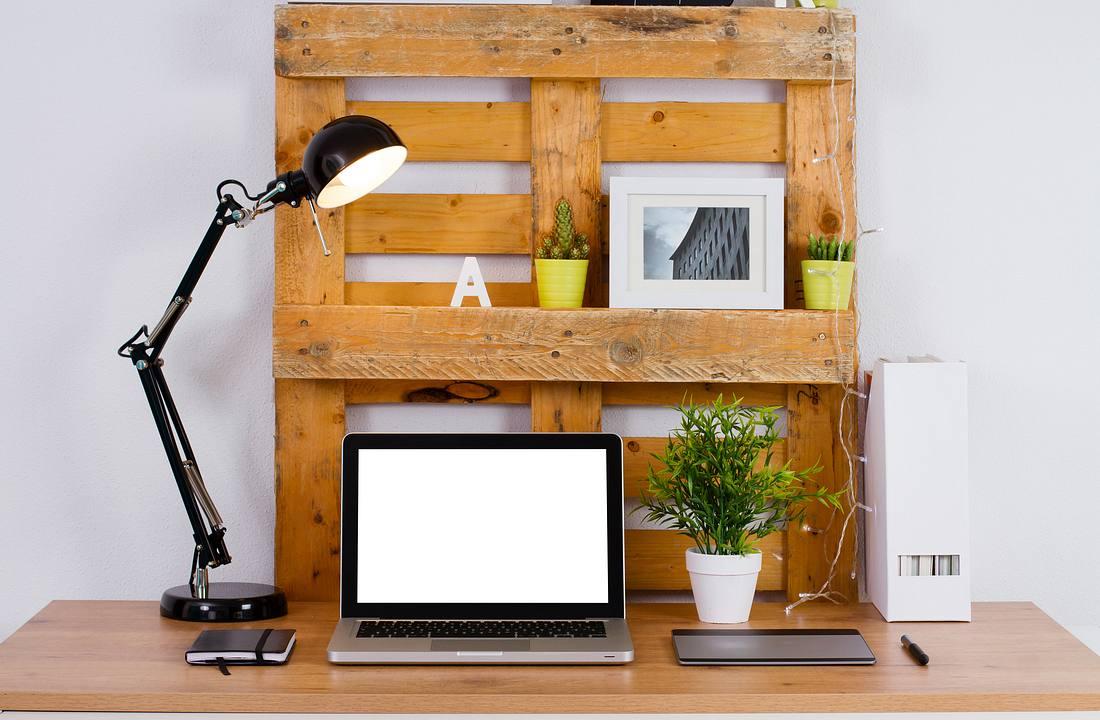 Schreibtisch mit Laptop, Holzpaletten und weiteren Utensilien