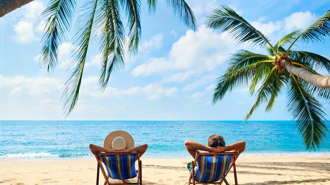 Zwei Urlauber am Strand unter Palmen in Liegestühlen - Foto: IMAGO / Stefan Zeitz
