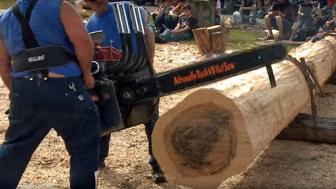 Timbersports-Aktive zerteilen Baumstämme mit einer V8-Kettensäge