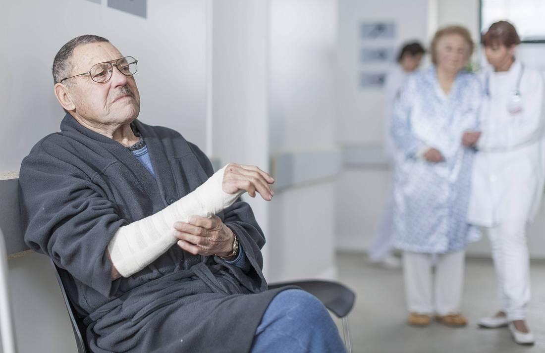 Älterer Mann mit gegipstem Arm im Krankenhaus