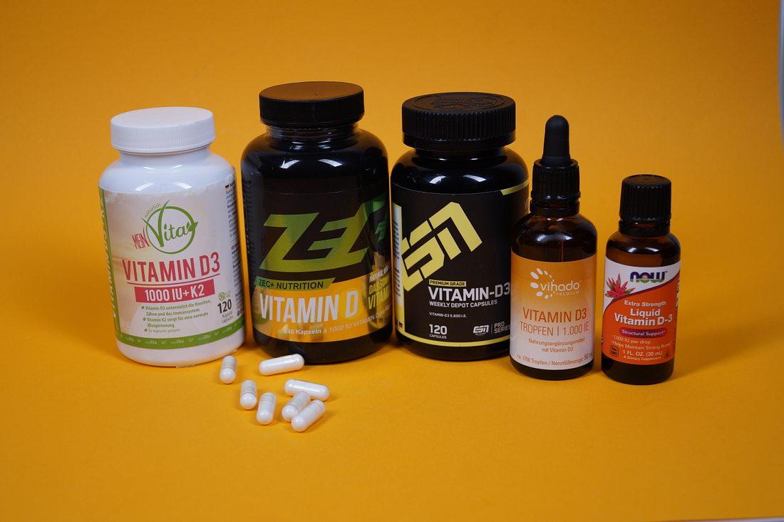 Fünf verschiedene Vitamin D-Präparate auf gelbem Hintergrund