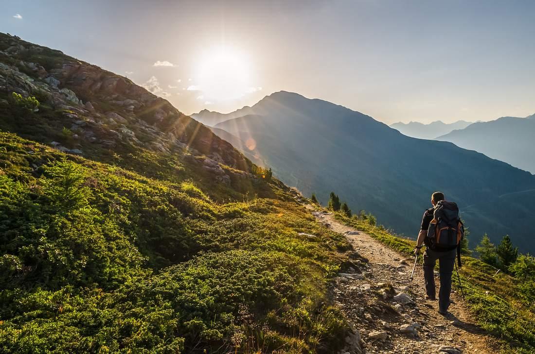 Ein Mann mit Rucksack wandert bei Sonnenschein durch eine Berglandschaft
