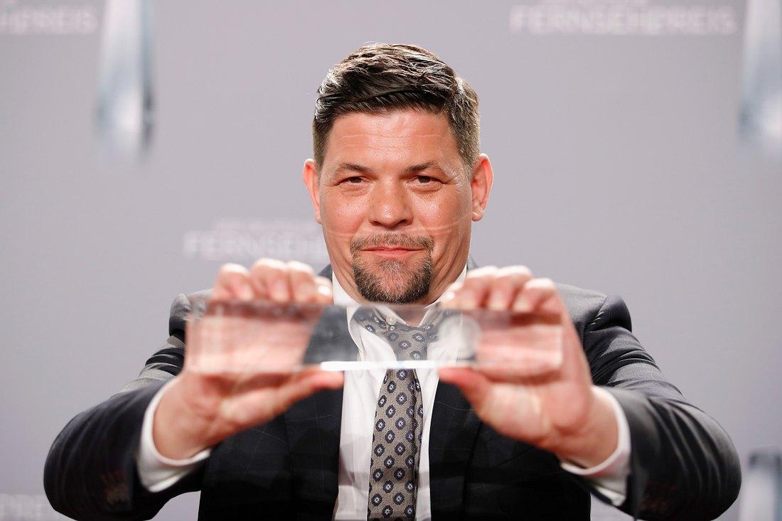 Tim Mälzer hält seinen Deutschen Fernsehpreis in die Kamera
