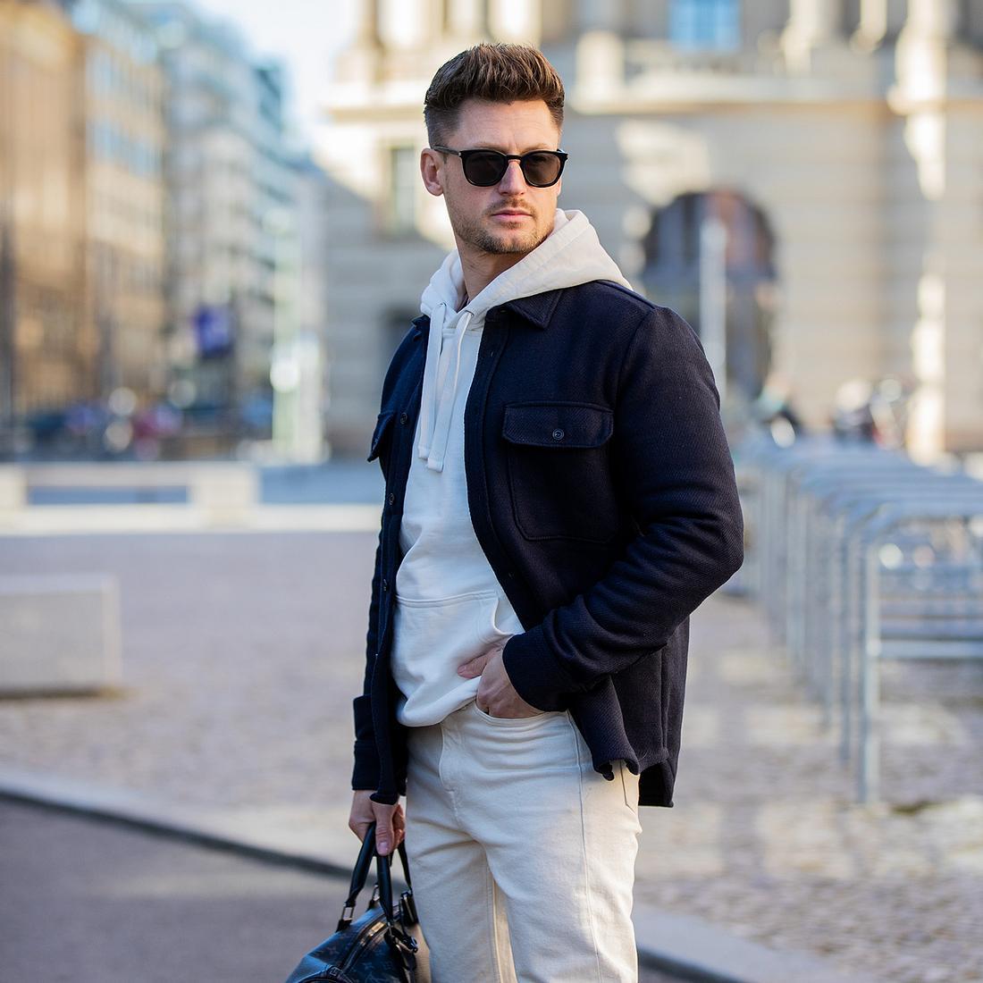 Streetstyle-Foto auf dem Mann weißen Hoodie unter einer navy-blauen Jacke trägt.