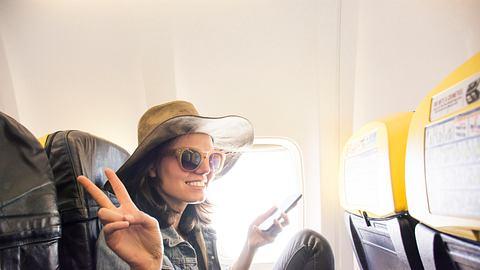 Jugendliche mit Hut und Sonnenbrille im Flugzeug macht Peace-Zeichen - Foto: iStock / Elitsa Deykova