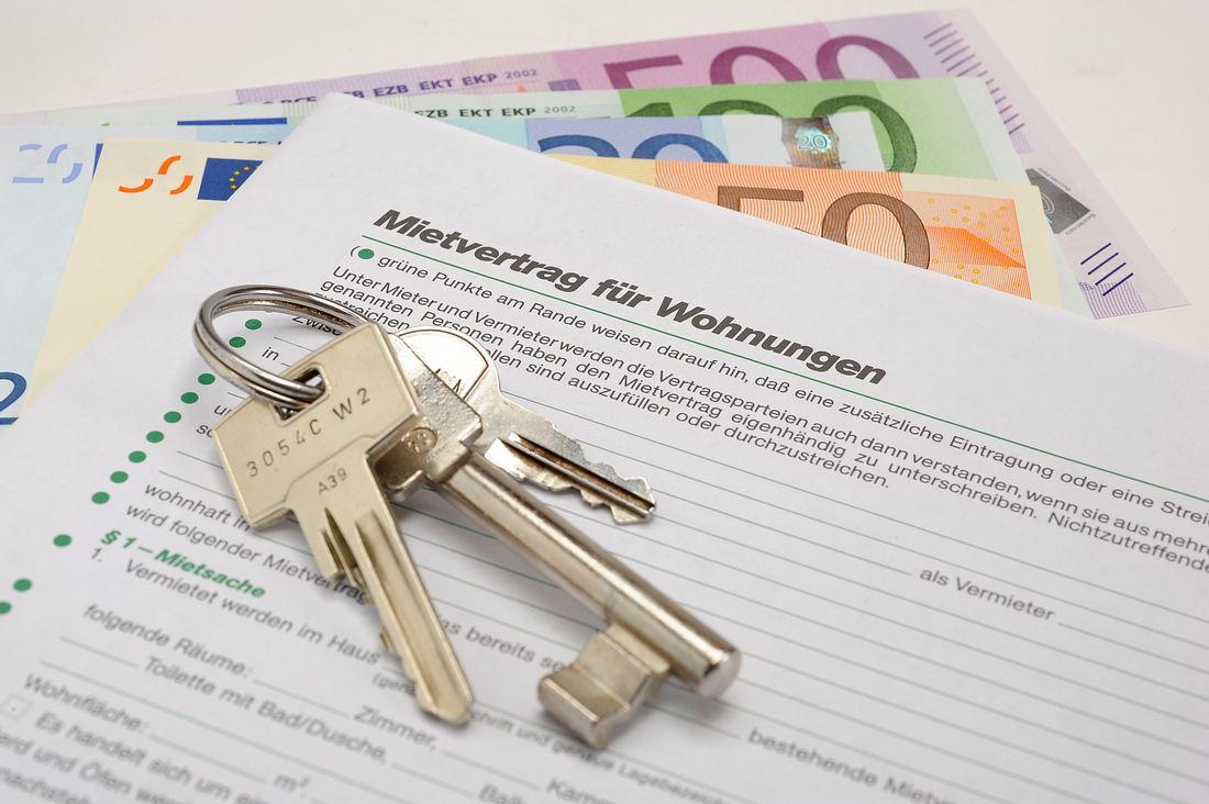 Schlüsselbund auf einem Mietvertrag und Geldscheinen