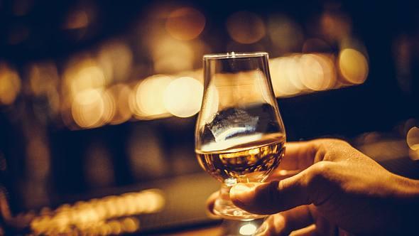 Hand holding a Glencairn single malt whisky glass - Foto: iStock / bizoo_n