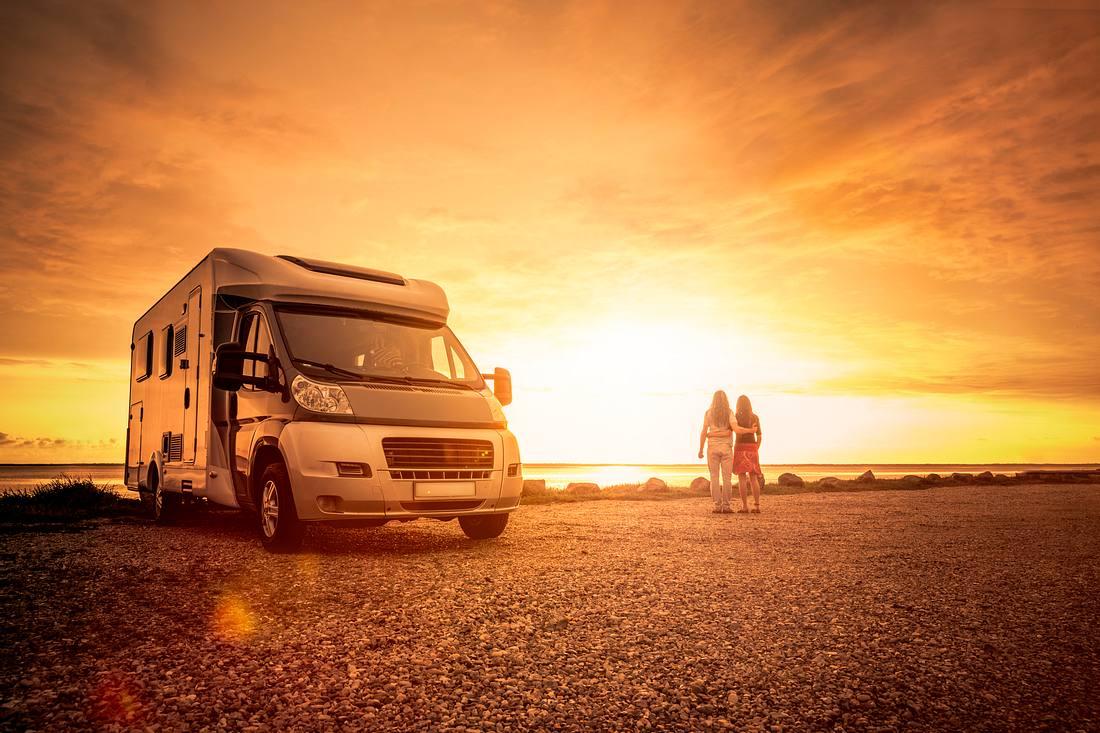 Pärchen vor Sonnenuntergang am Strand - inklusive Wohnmobil