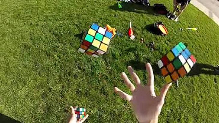 Ravi Fernando löst drei Zauberwürfel, während er mit ihnen jongliert