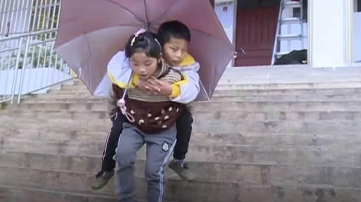 Zhou trägt ihren Bruder zur Schule